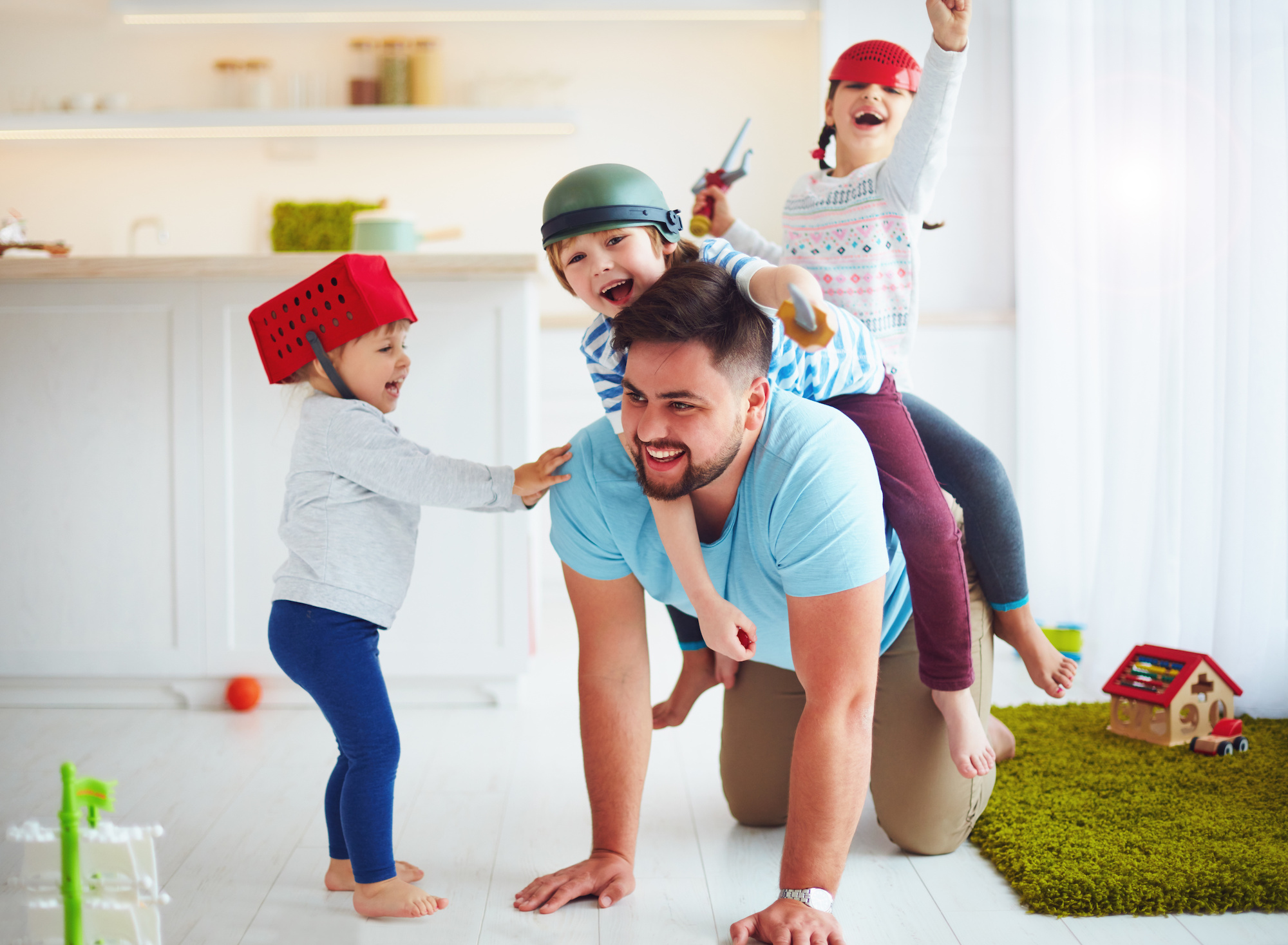 Man with his kids crawling over him who needs a vasectomy | Urology Associates | Denver, CO